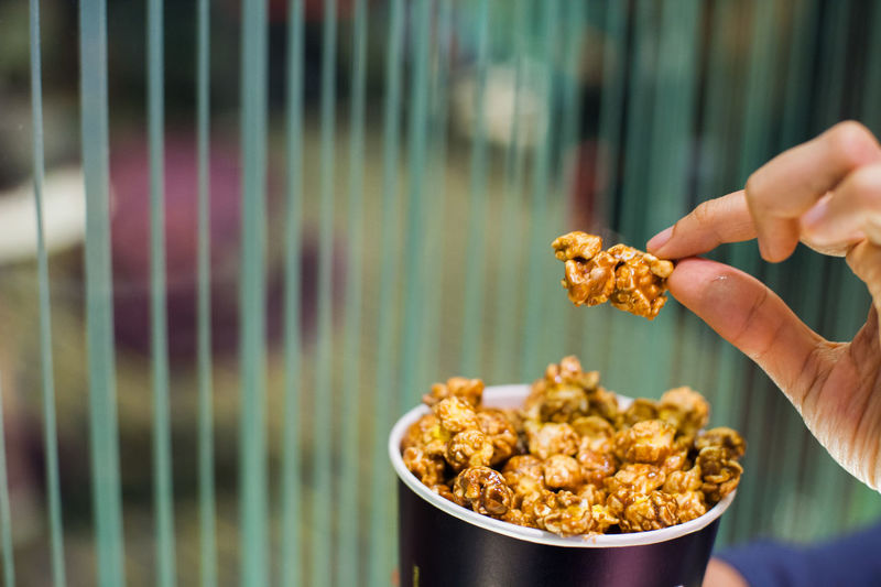 Close-up of hand holding caramel popcorn at theatre