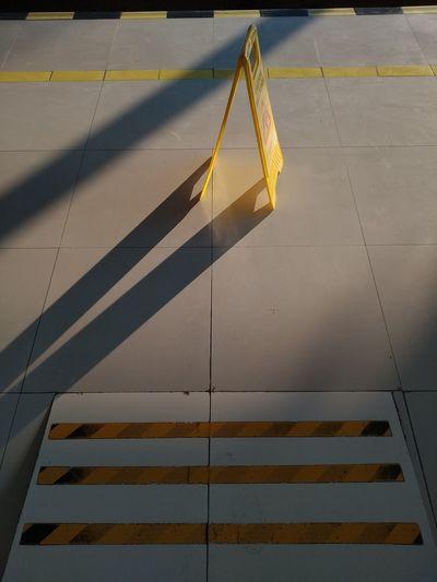 High angle view of yellow flag on tiled floor