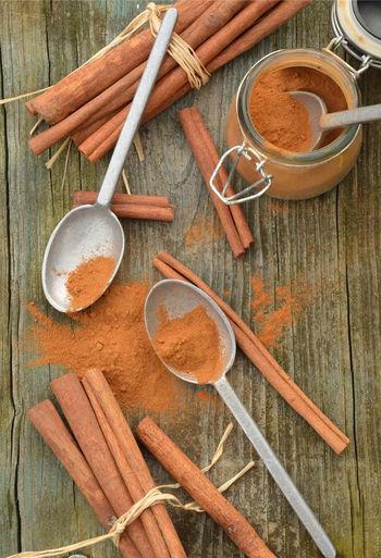 Cinnamon powder spice, cinnamon sticks, spice jar, pewter spoons,