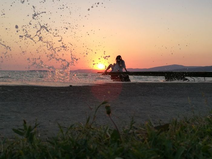 Water Splashing At Beach By Woman Relaxing On Pier During Sunset