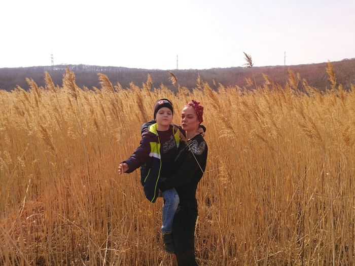 Woman carrying son while standing amidst crops on field against sky