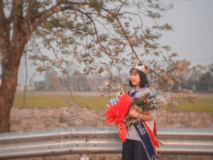 Side view of young woman holding bouquets standing against sky