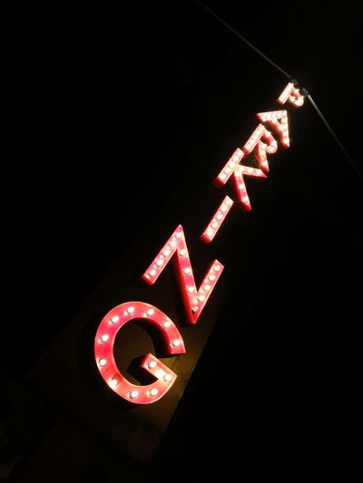 Low angle view of illuminated neon sign at night