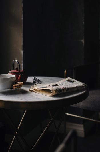 Close-up of food and drink with newspaper on table