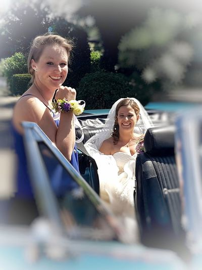 Focus on bride in back of car and bridesmaid showing her flower bracelet and about to get seated as well. Both happily smiling into camera... Romance People Females EyeEm Selects Young Women Friendship Blond Hair Smiling Togetherness Happiness Wedding Dress Women