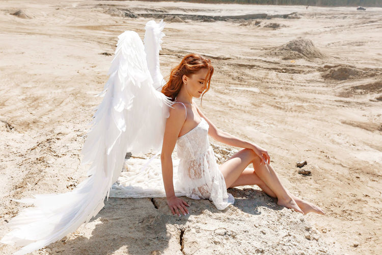 Woman with white wings on beach