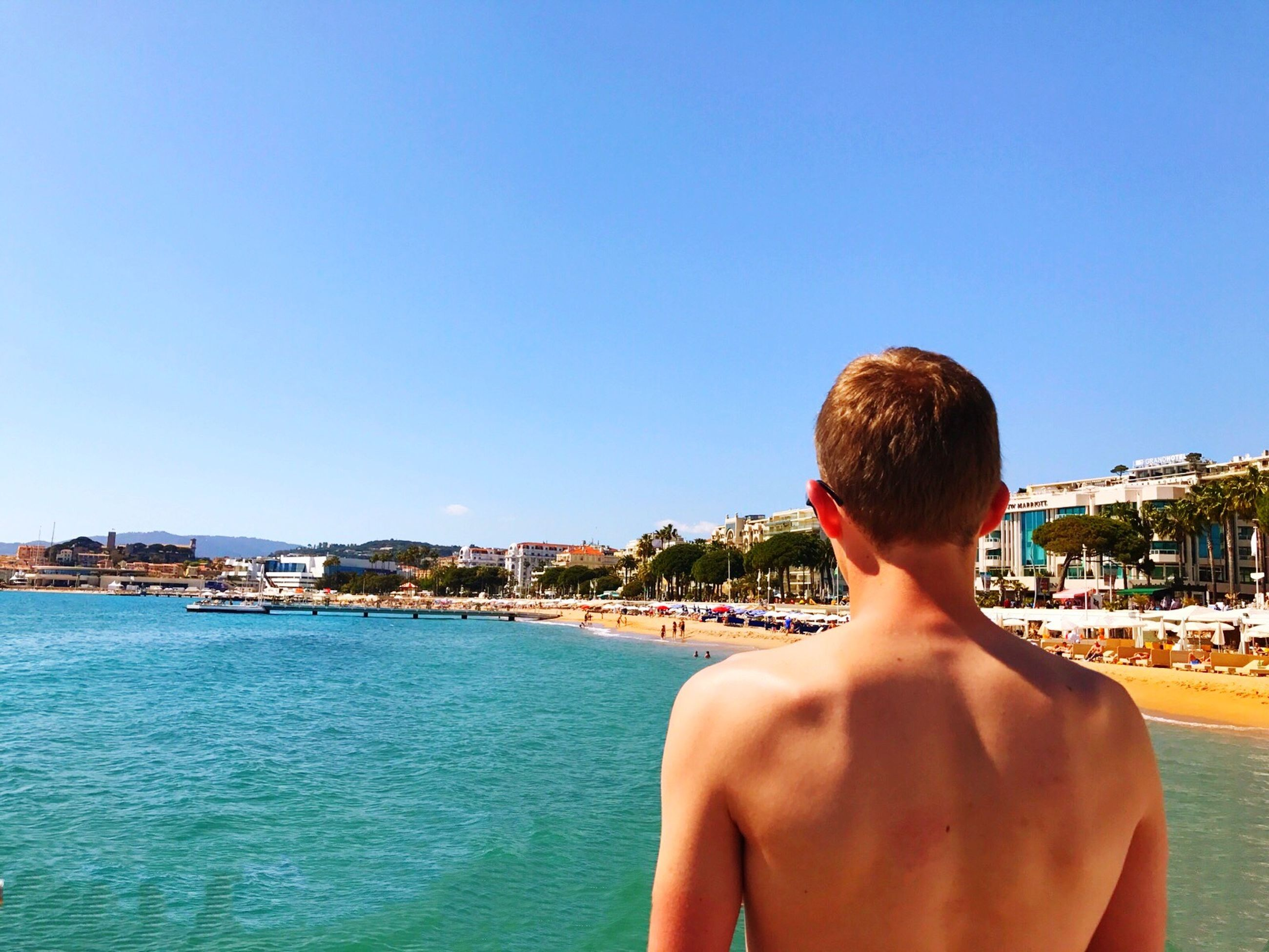 rear view, water, sea, one person, blue, clear sky, leisure activity, lifestyles, day, sunlight, outdoors, shirtless, headshot, vacations, real people, beauty in nature, sky, scenics, swimming pool, beach, horizon over water, young adult, men, adult, one man only, nature, adults only, people, only men