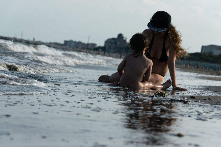 Mother sitting with child on shore at beach