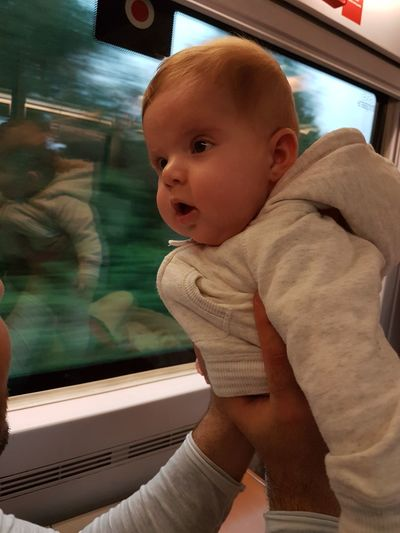 Baby girl looking through window while traveling in train