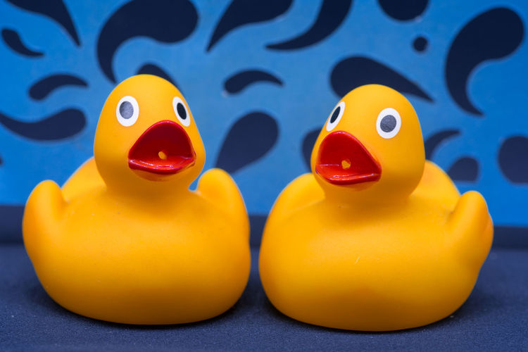 Close-Up Of Yellow Rubber Ducks On Blue Textile