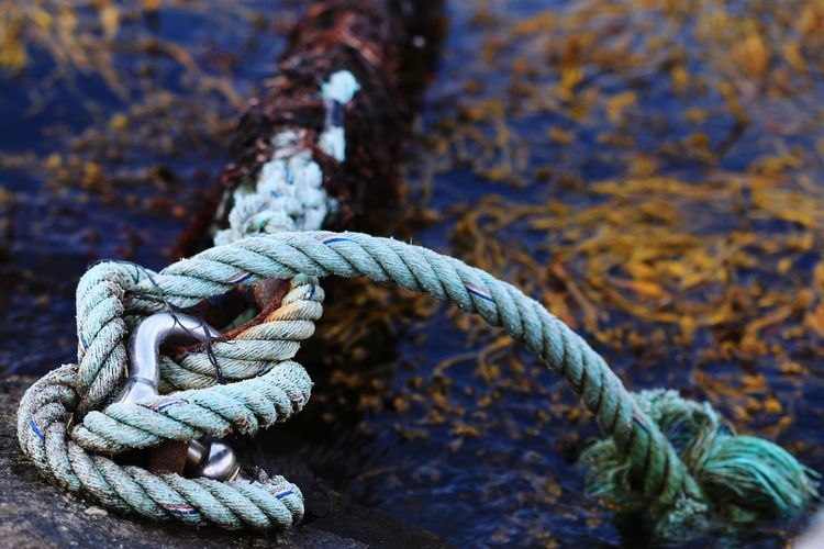 Close-up of rope tied on metal at shore