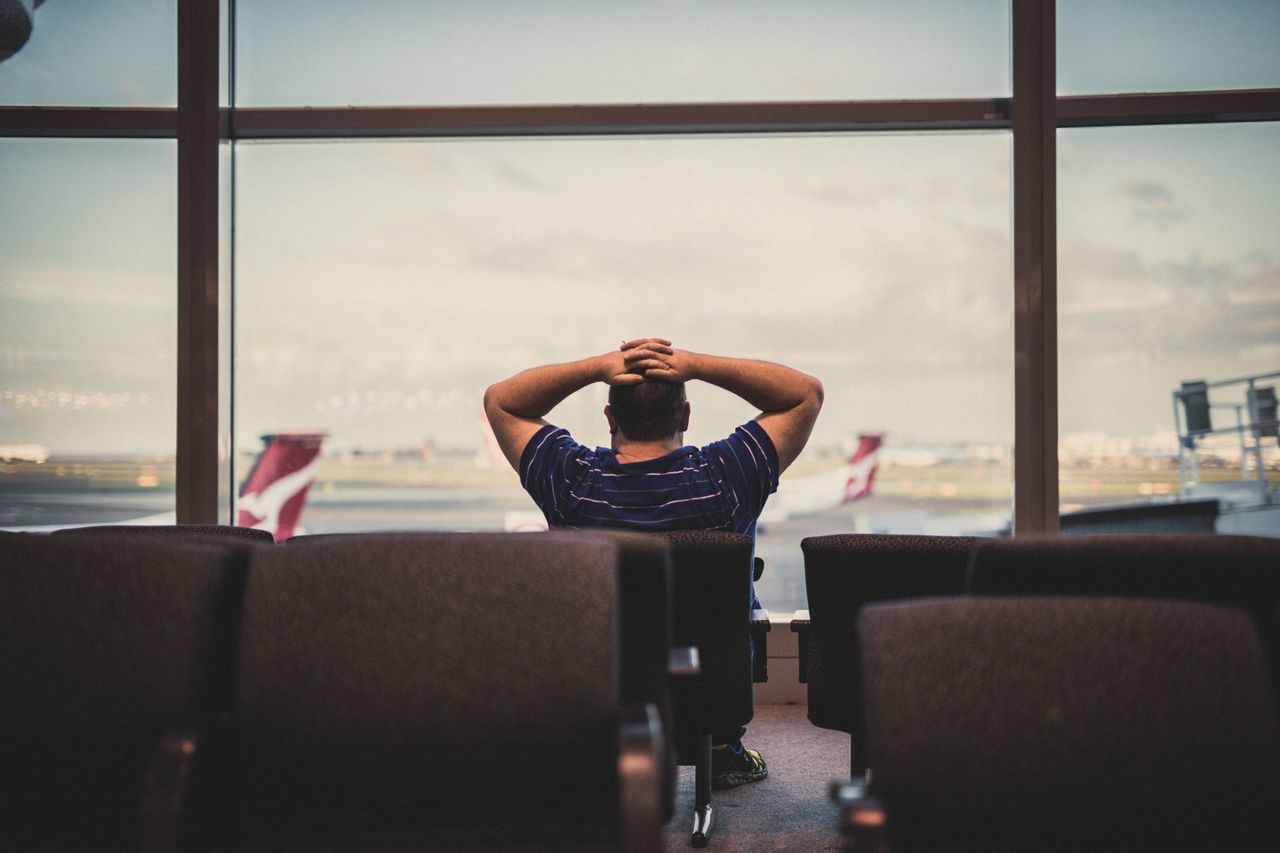 MAN SITTING AT AIRPORT
