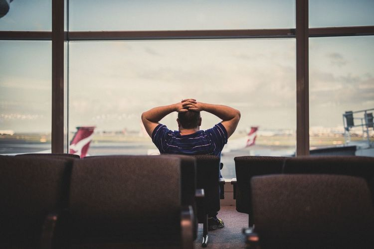 Young man sitting at airport against sky