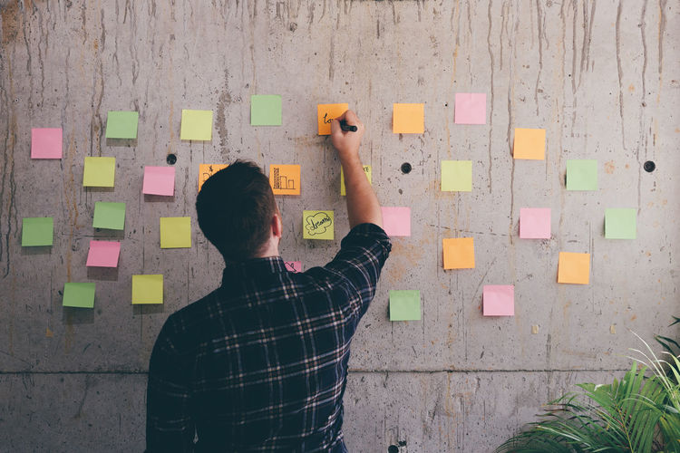 Rear View Of Man Writing On Adhesive Note In Office