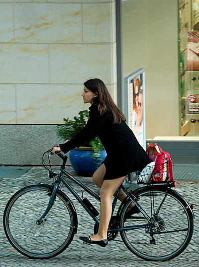 a young woman coming from shopping riding on her bike Bicycle Bicycles Bike Einkauf Fahrrad Fashion Frau Fun Happiness Legs Lifestyles Long Hair Motion Real People Shopping Side View Trasportation Young Women