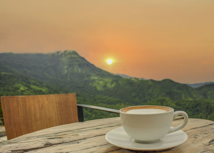Coffee cup on table against sky during sunset