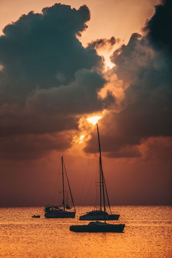 Silhouette boats in sea against dramatic sky