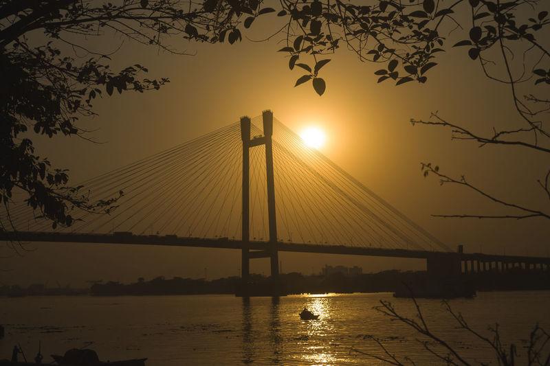 Silhouette of suspension bridge at sunset