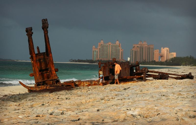 People By Shipwreck At Beach Against Sky
