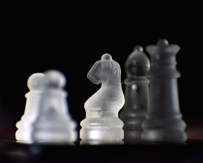 Close-up of chess pieces on table against black background
