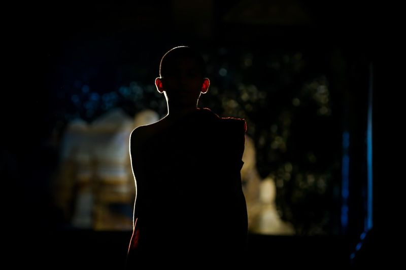 Rear View Of Silhouette Monk At Night