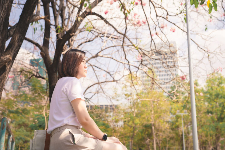 Woman looking away while sitting on tree