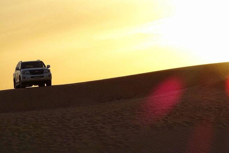 Car on desert land during sunset