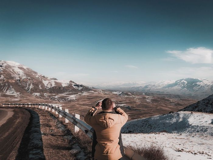 Rear view of man photographing while standing by railing during winter