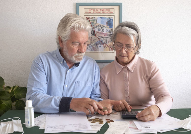 Senior couple counting money on table at home