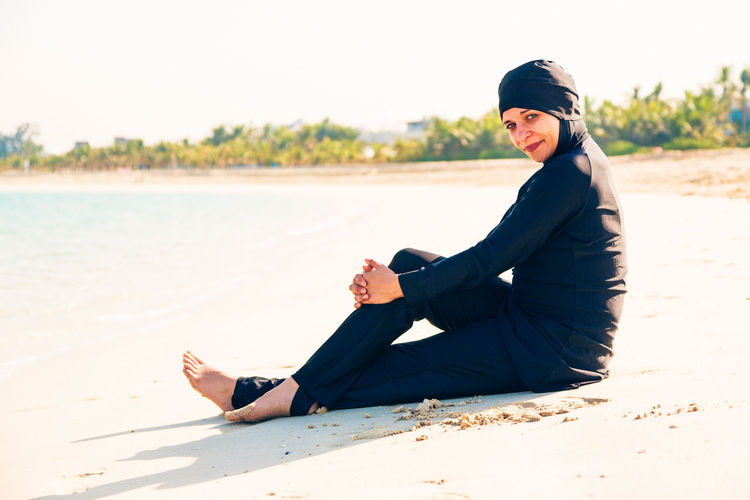 Portrait of smiling woman on beach against clear sky