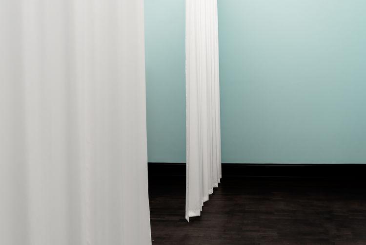 White curtain on hardwood floor against wall