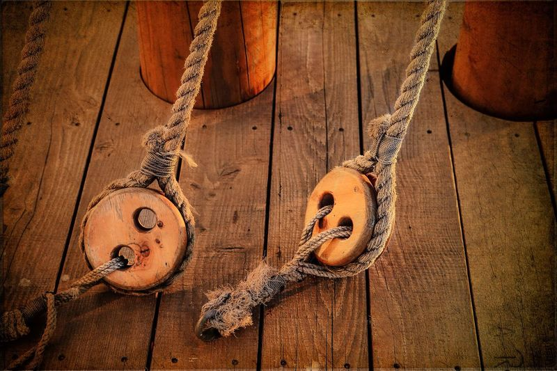 Ropes tied to wooden pulley in boat