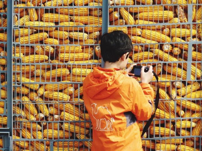 Boy photographing corns at supermarket