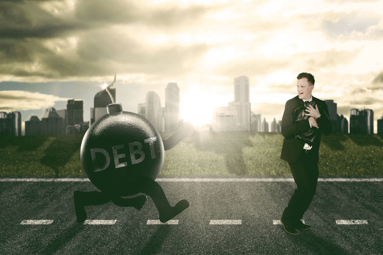 Digital composite image of explosive equipment running towards businessman in city during sunset