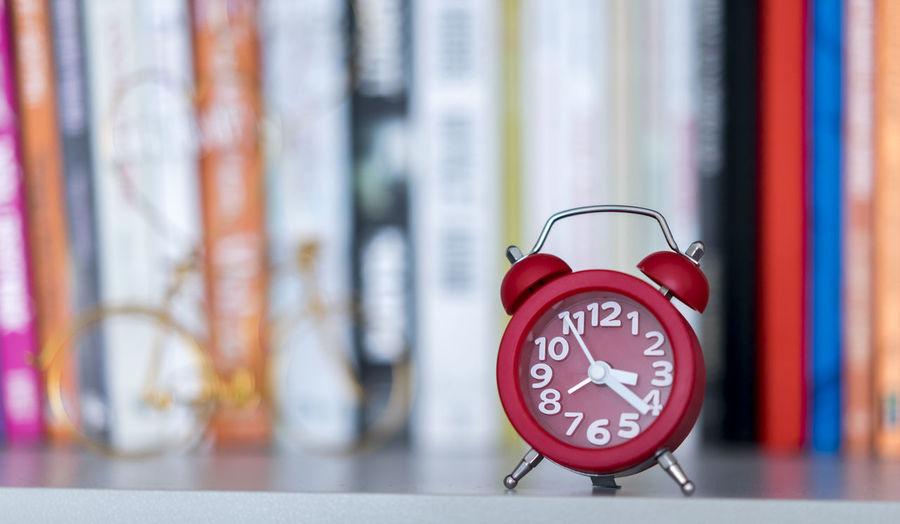 Close-Up Of Alarm Clock Against Books