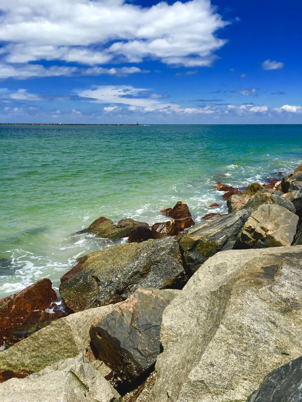 Scenic View Of Rocks On Shore By Sea Against Sky