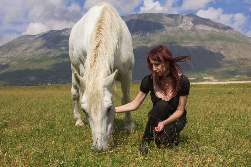 Woman with white horse on field against mountain