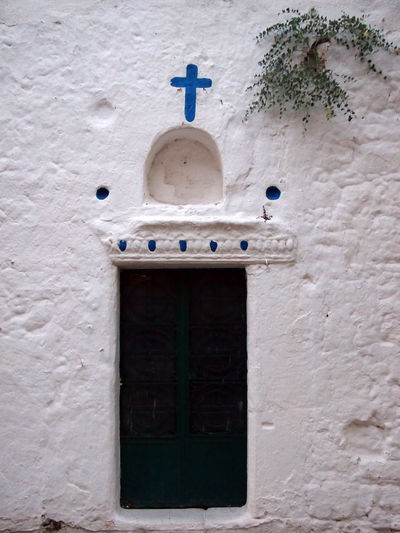entrance to an old village church in Kos Greece Church Cross Arch Architecture Belief Blue Building Building Exterior Built Structure Closed Cross Day Door Entrance Greece Kos Low Angle View No People Place Of Worship Religion Spirituality Wall - Building Feature White Background Window