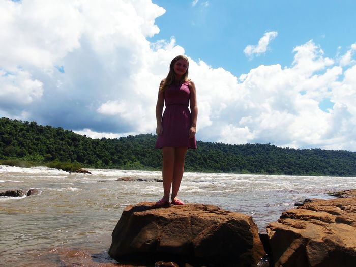 Low Angle View Of Young Woman Standing On Rock Against River