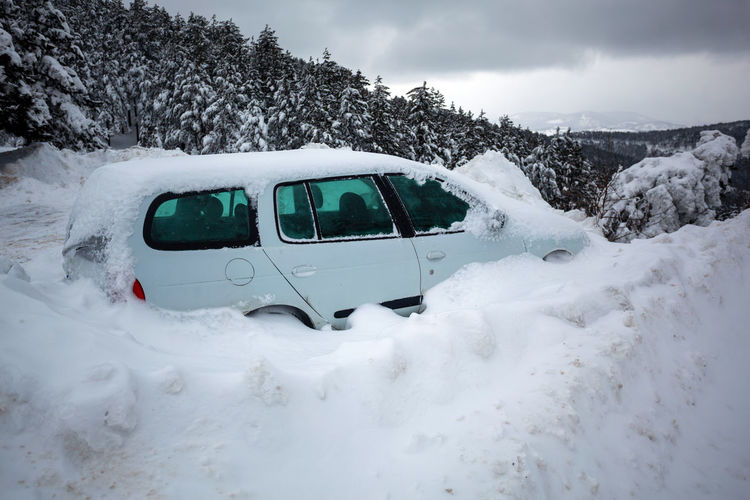Car stuck in deep snow on mountain road - winter traffic problem stock image