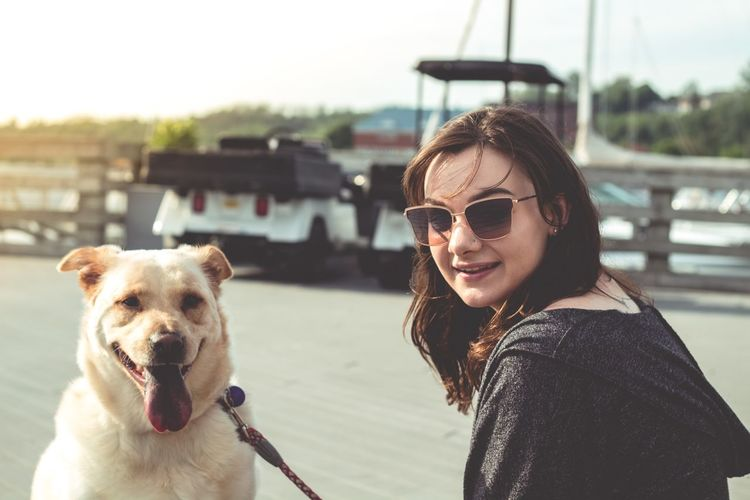 Portrait Of Smiling Young Woman Holding Dog At Beach