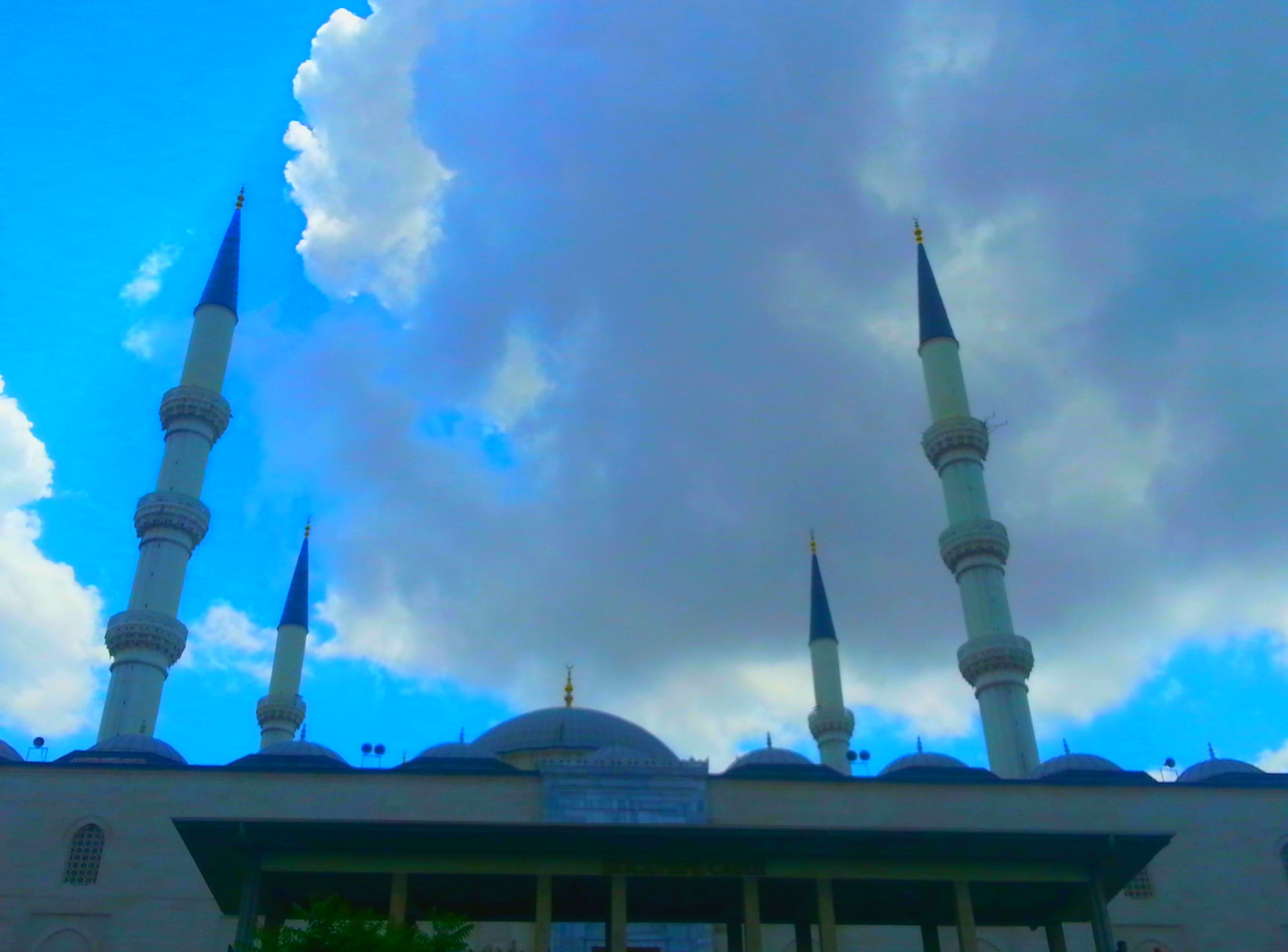 architecture, building exterior, built structure, blue, low angle view, sky, cloud - sky, cloud, outdoors, day, no people, tower, religion, sunlight, city, cloudy, high section, building, place of worship, mosque