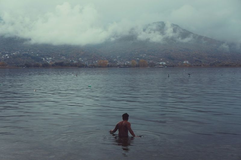 Rear view of man swimming in lake against mountain
