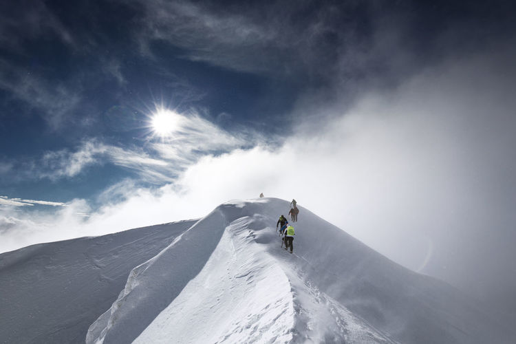 Low Angle View Of People Skiing On Snow Covered Mountain