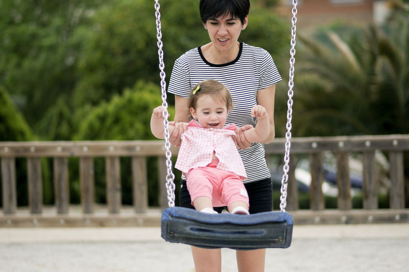 Mother swinging cute baby girl at park