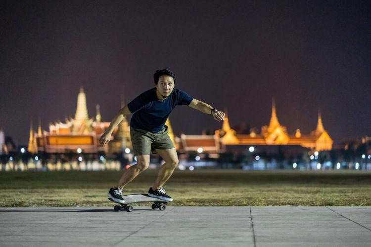 Full length of man skateboarding on city street at night