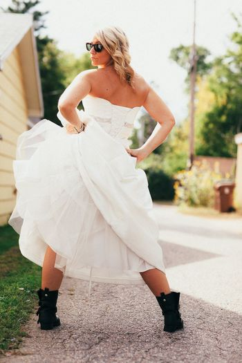 Rear view of playful bride in wedding dress standing on road