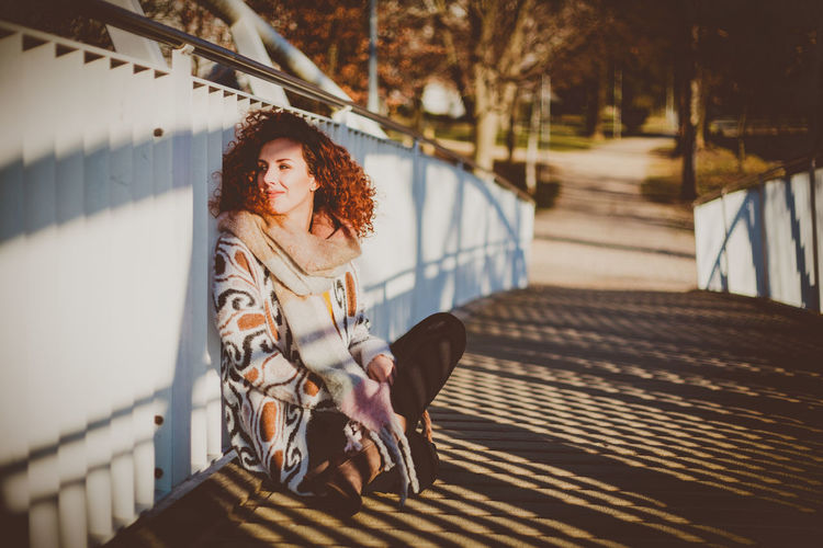 Woman Sitting On Footbridge