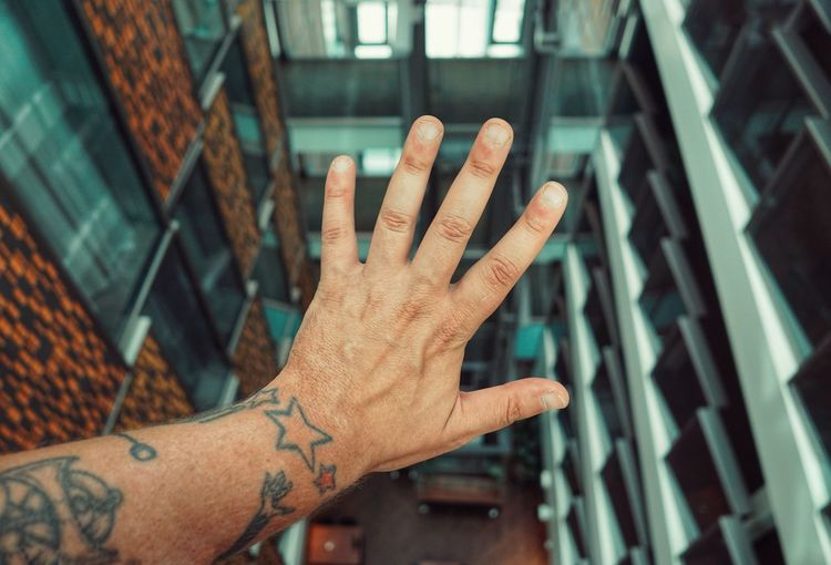 Cropped hand of man gesturing against building