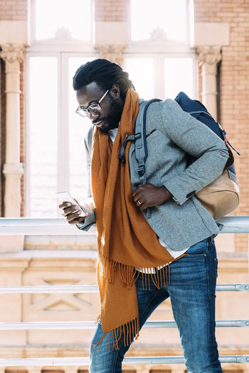 Man Using Mobile Phone While Walking In Corridor